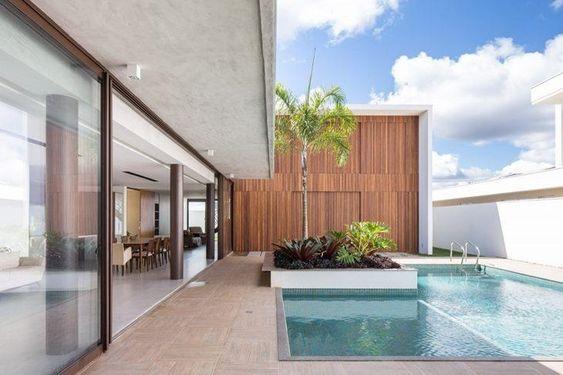 casa em L com piscina e painel de madeira