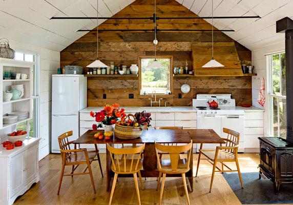 Cozinha com móveis brancos, exceto a mesa amadeirada.