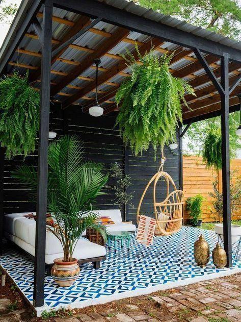 Varanda com sofá branco e plantas suspensas.