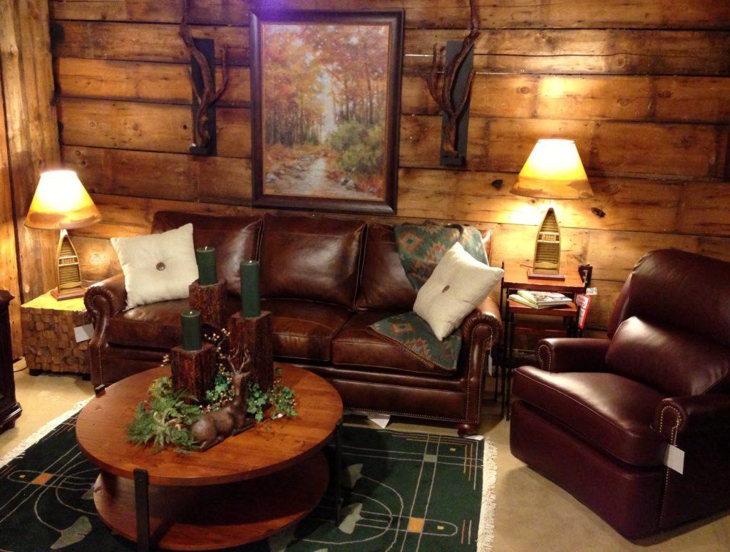 Sala com sofá e poltrona de couro e mesa de centro de madeira.