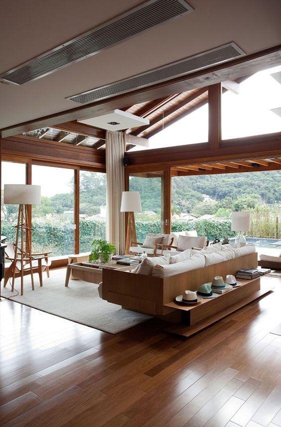Sala de estar com vista para a área externa e móveis brancos e marrons.