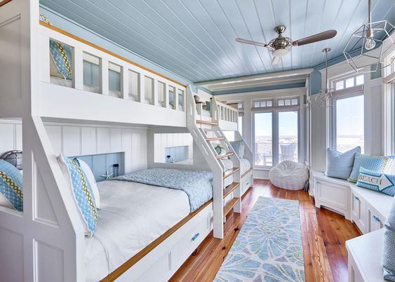 Quarto branco e azul com muitas camas.