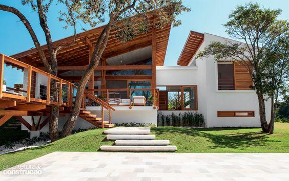 Casa grande e moderna branca com detalhes de madeira.