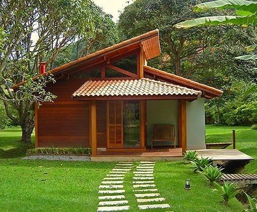 Casa de madeira com caminho de pedra na grama.