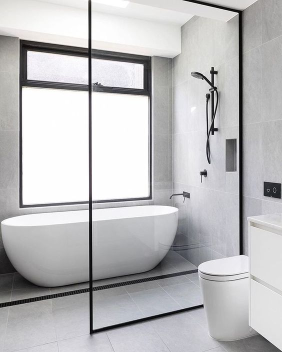 parede de vidro com esquadria de metal pedra e banheira oval