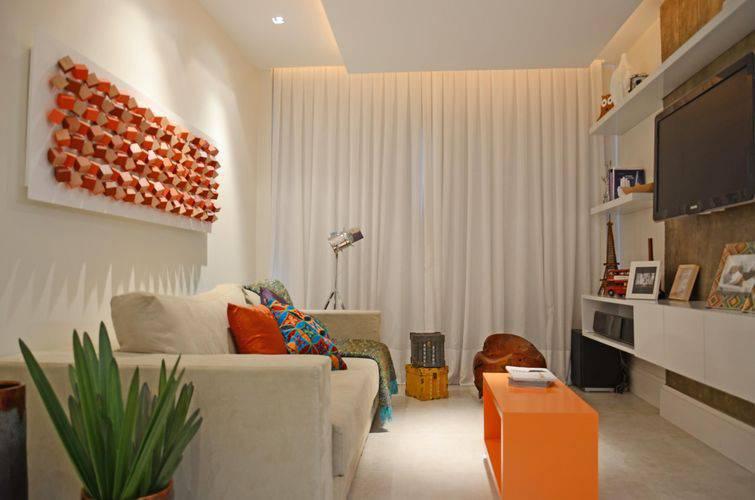 Decoração simples com sofá bege e mesa de centro laranja.