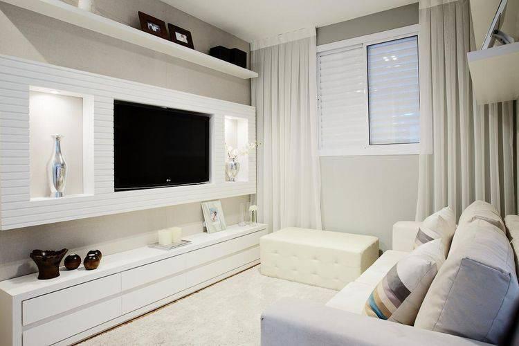 Decoração branca com sofá branca e rack.