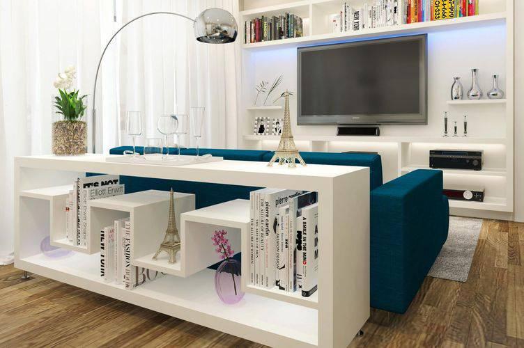 Decoração simples com sofá azul e prateleiras para livros.
