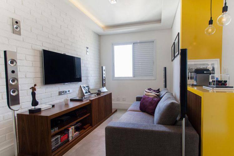 Decoração simples com rack de madeira, sofá cinza e parede de tijolinho branco.