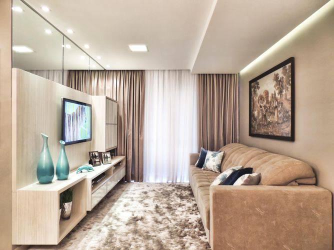 Decoração com tapete felpudo, sofá bege e espelho.