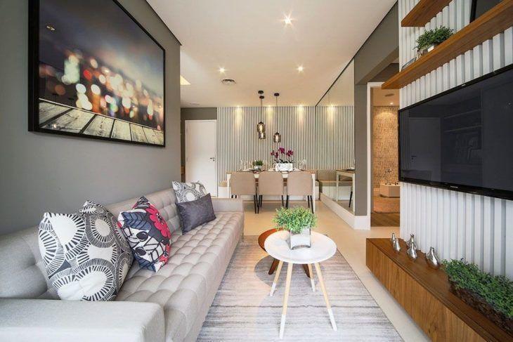 Decoração moderna com sofá cinza e rack de madeira.