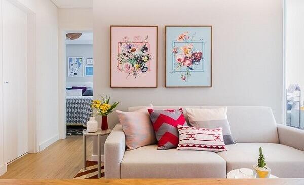 Decoração simples com quadros delicados e sofá cinza.