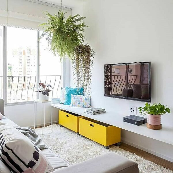 Decoração simples com sofá cinza e vasos de planta.