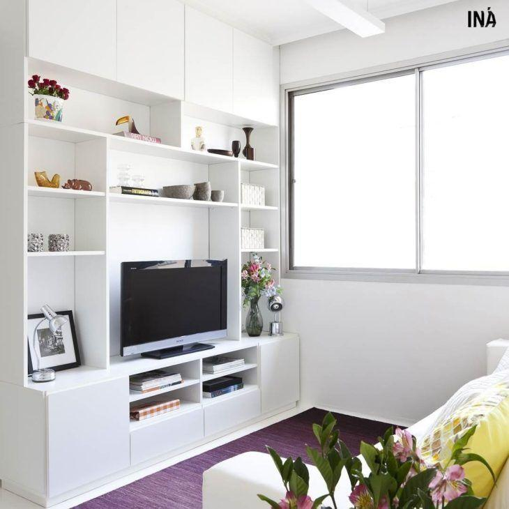 Decoração com rack branco, nichos e tapete roxo.