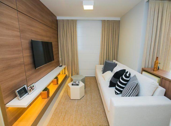 Decoração simples com sofá branco e painel de madeira.