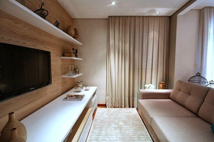 Decoração simples com painel de madeira e sofá bege.