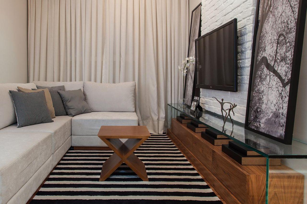 Decoração com sofá cinza, tapete preto e branco e parede de tijolinho branco.