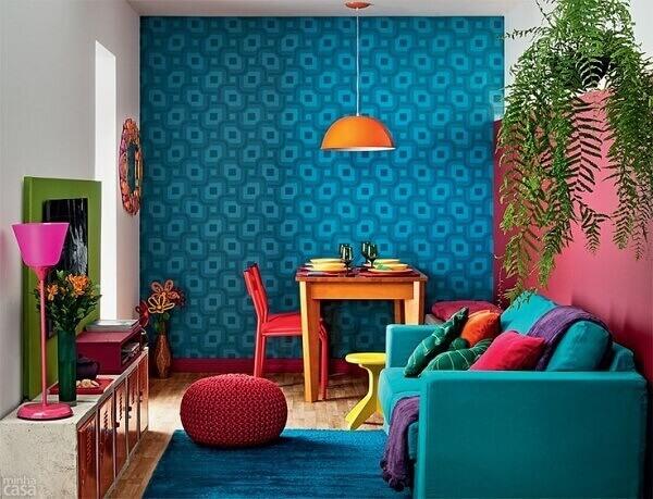 Decoração moderna e colorida com sofá azul, papel de parede decorado, painel de madeira verde e vaso de planta.