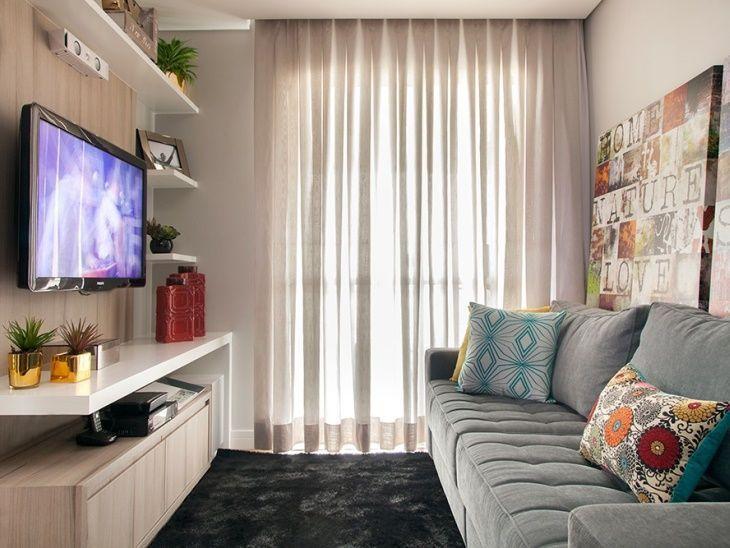 Decoração simples com sofá cinza, tapete preto e quadros.