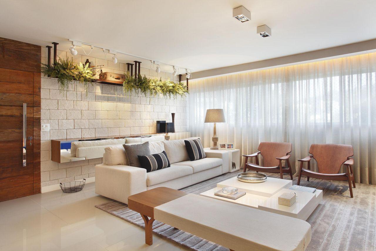 Decoração com sofá branco, cadeira moderna, vasos de planta.