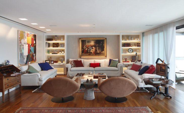 Decoração elegante com sofá branco, poltronas giratórias e quadros.