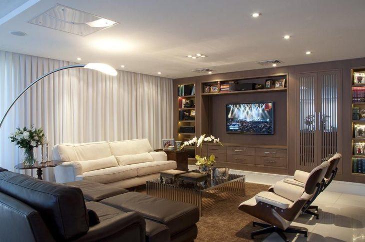 Decoração moderna com sofá branco, sofá de couro e poltronas giratórias.