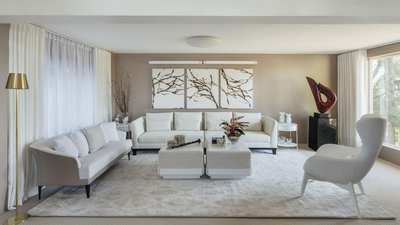 Decoração clean com sofás brancos, parede bege e poltrona moderna.
