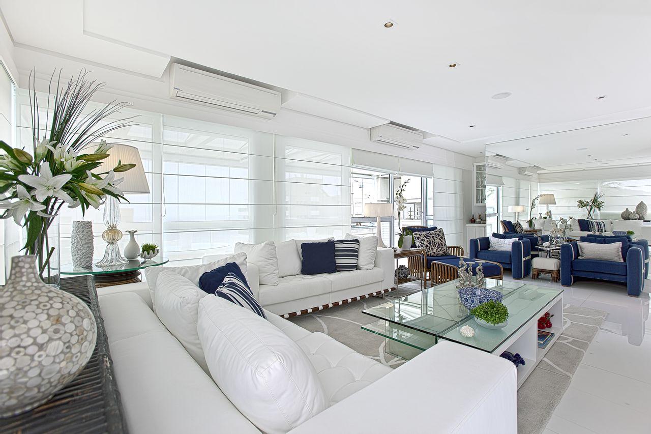 Decoração luxuosa com sofá branco e poltronas azuis.