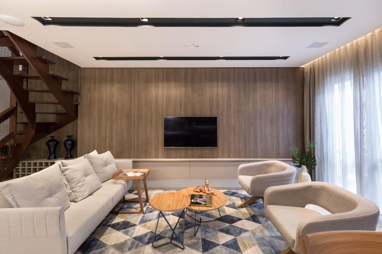 Decoração moderna com sofá branco, tapete geométrico e painel de madeira.