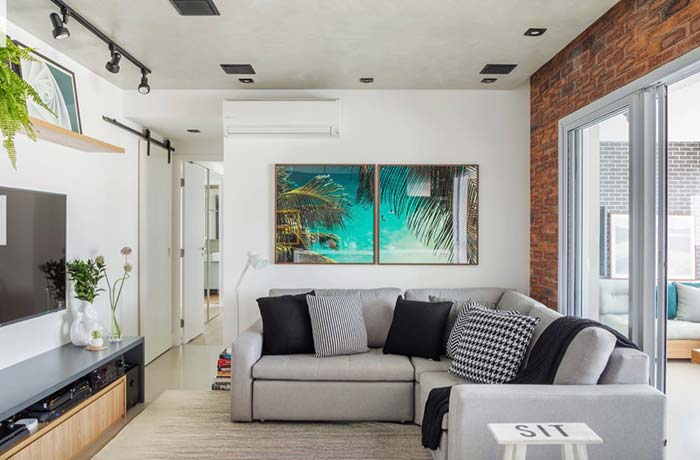Decoração simples com sofá em L cinza e parede de tijolinho aparente.