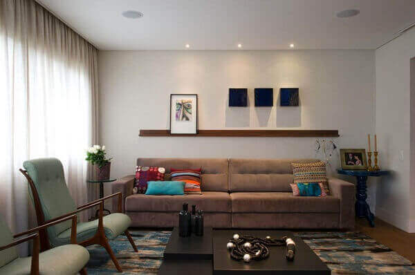 Decoração moderna com sofá marrom e poltronas modernas e mesa de centro preto.