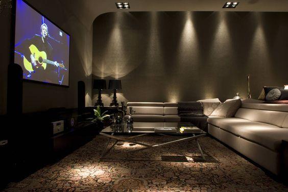 Decoração moderna com sofá cinza, tapete decorado e televisão.