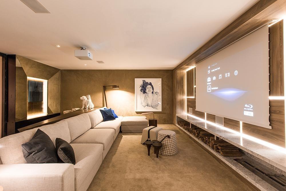 Decoração moderna com sofá bege, painel de madeira e projetor.