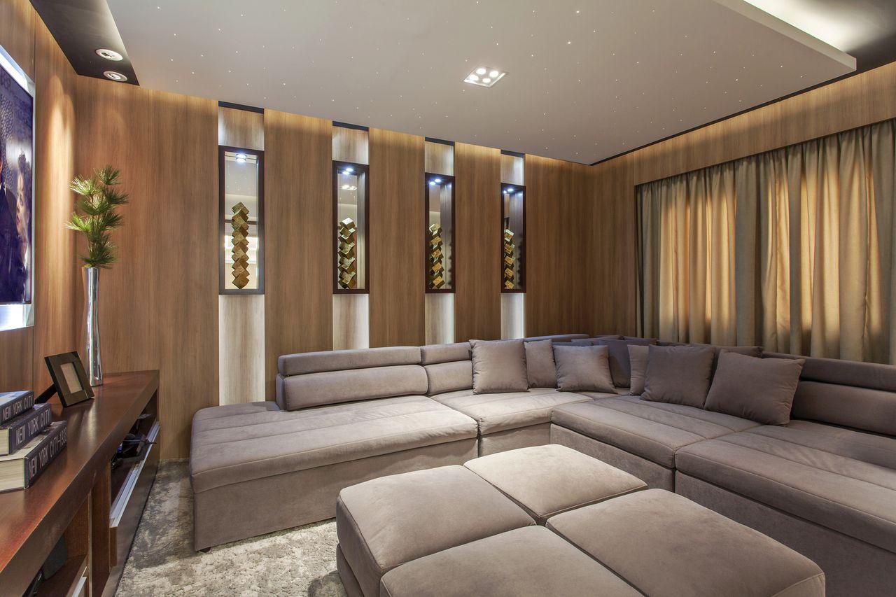 Decoração moderna com sofá em L, rack de madeira e esculturas decorativas.