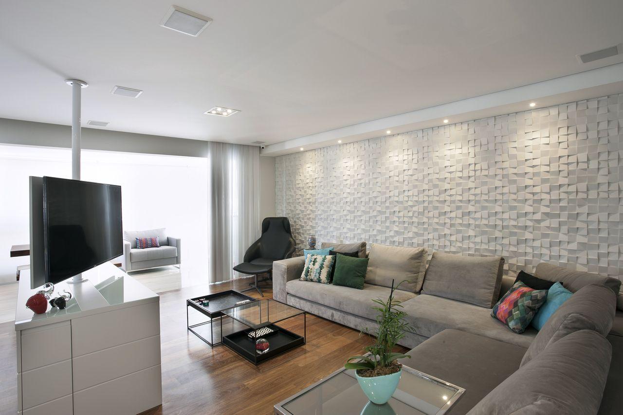 Decoração modera com sofá em L, azulejo tridimensional e televisão giratória.