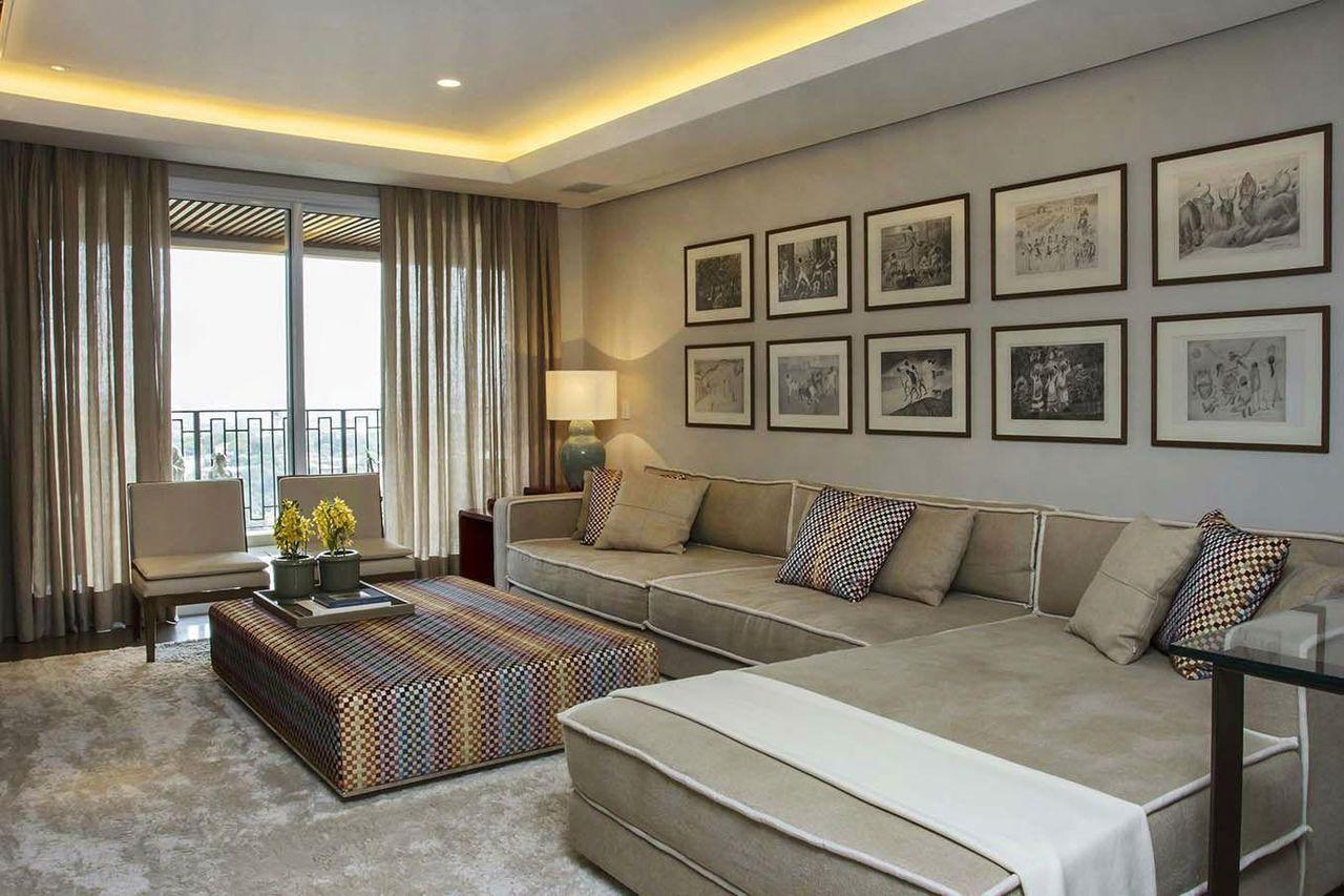 Decoração moderna com quadros, sofá bege e mesa de centro.