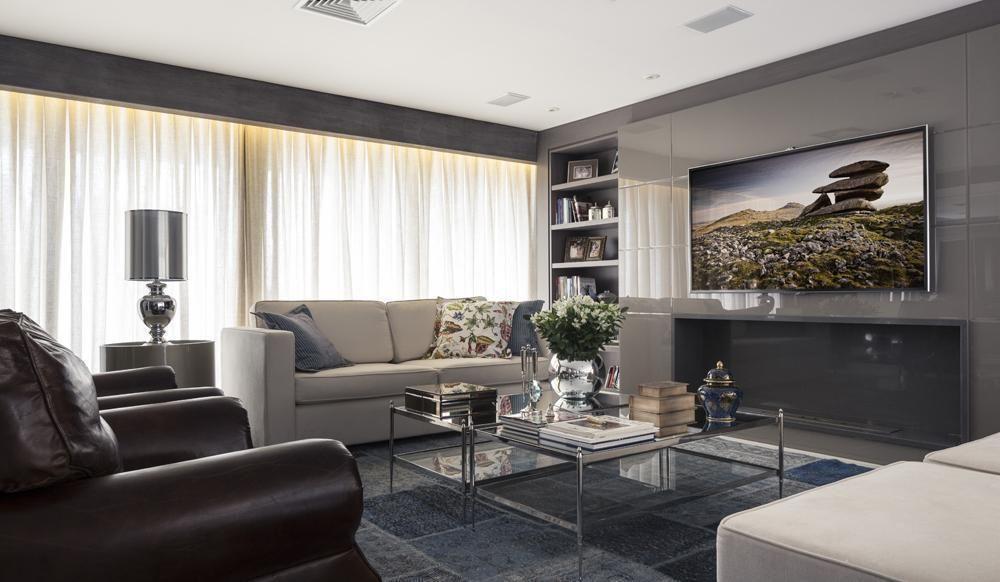 Decoração luxuosa com sofá bege, poltrona de cultura e mesa de centro de vidro.