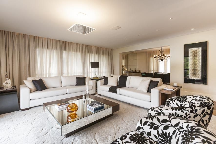 Decoração luxuosa com sofá branco, poltronas decorados e mesa de centro espelhado.