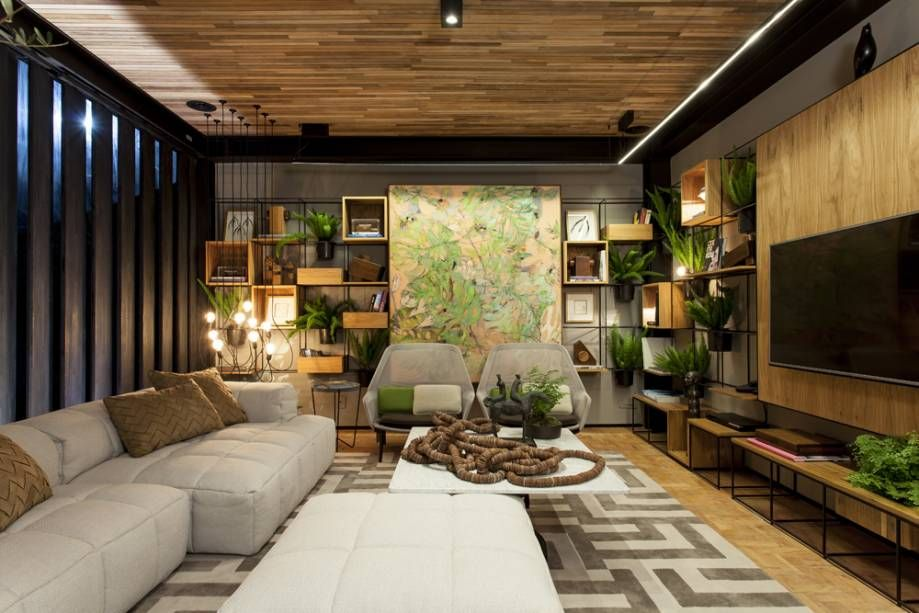 Decoração moderna com sofá cinza, painel de madeira, nichos e vasos de planta.
