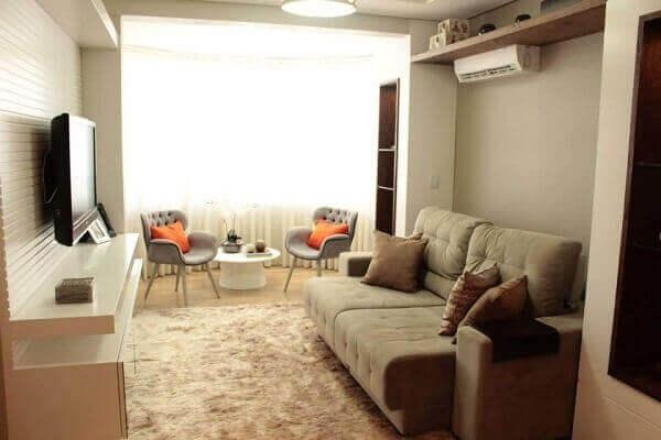 Como decorar uma sala simples com sofá bege e rack branco.