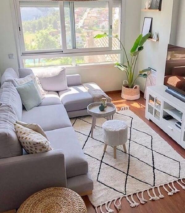 Como decorar uma sala simples com sofá em L, tapete geométrico e vaso de planta.