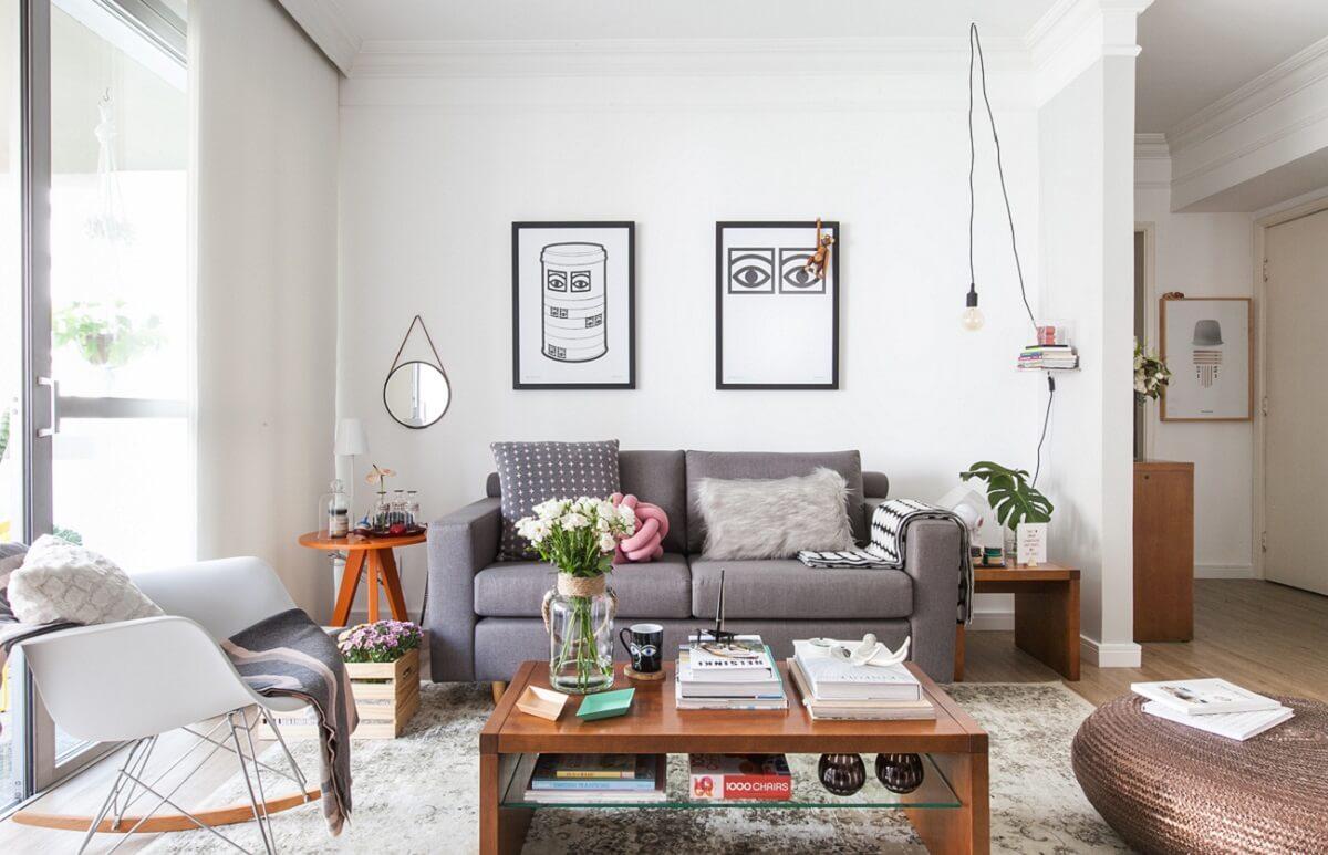 Como decorar uma sala simples com sofá cinza e mesa de centro de madeira.