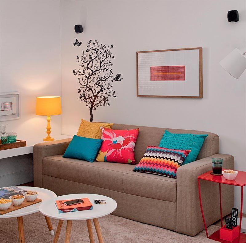 Como decorar uma sala simples com sofá bege, almofadas coloridas e adesivo na parede.