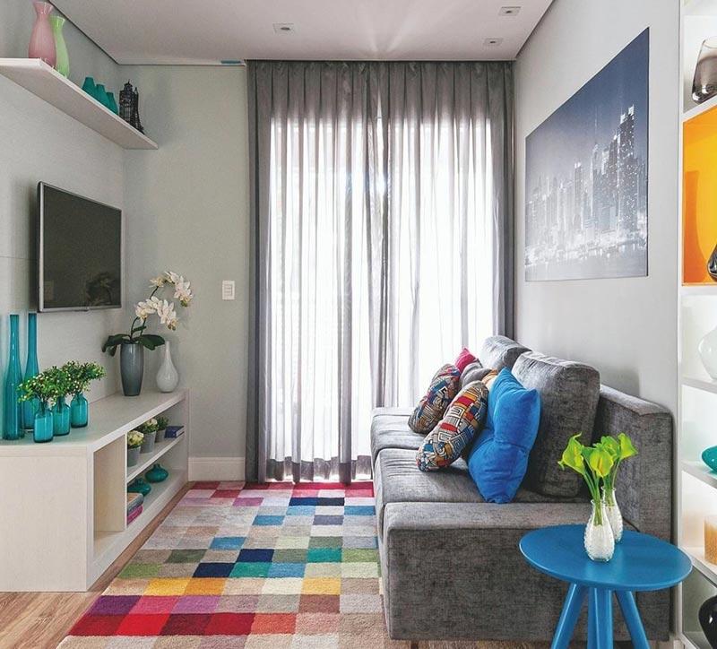 Como decorar uma sala simples com sofá cinza e tapete colorido.