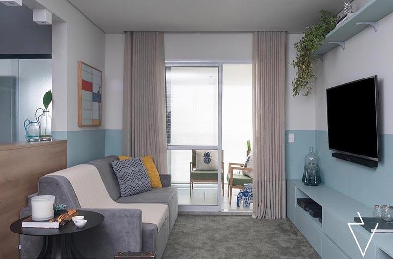 Como decorar uma sala simples com sofá cinza e rack azul.