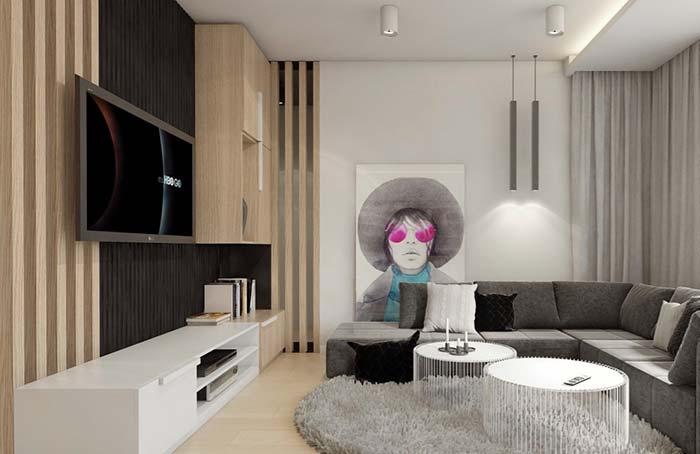 Como decorar uma sala moderna com sofá cinza, painel de madeira e tapete felpudo.