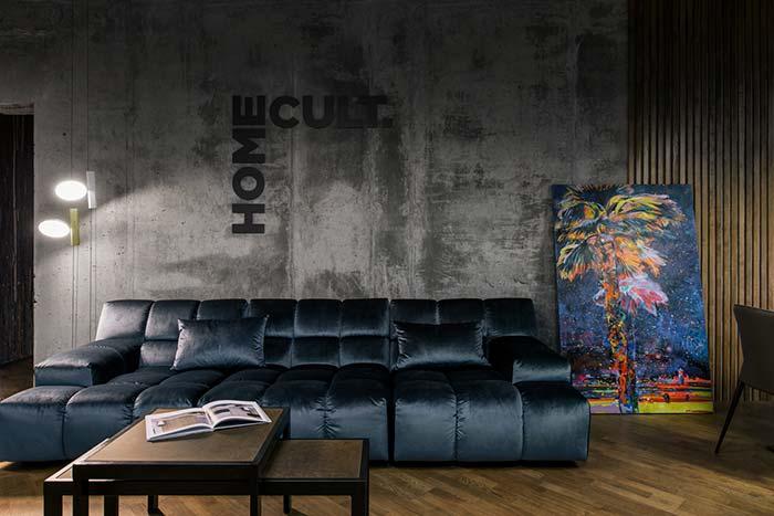 Como decorar uma sala moderna com parede de cimento queimado e sofá azul.