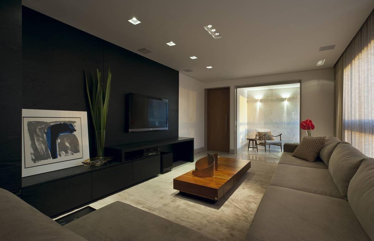 Como decorar uma sala moderna com sofá bege e rack preto.