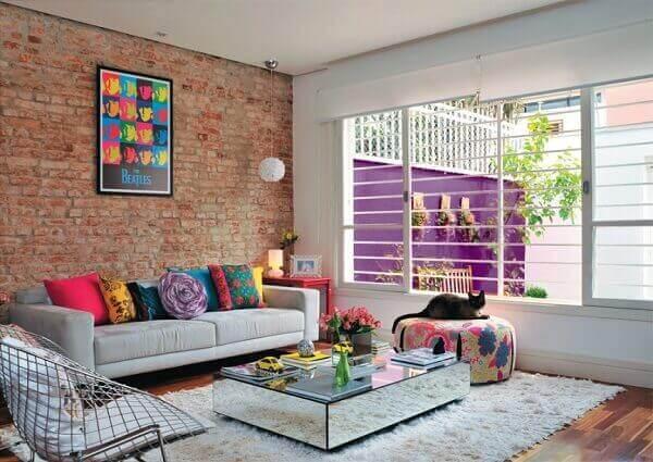 Como decorar uma sala moderna com sofá cinza, parede de tijolinho aparente, almofadas coloridas e mesa de centro espelhado.
