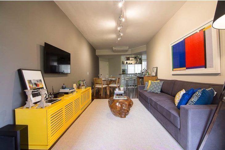 Como decorar uma sala moderna com sofá cinza, rack amarelo e mesa de centro de madeira.